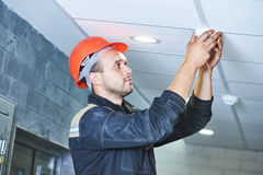 Arbeitskraft, die Rauchmelder auf die Decke installiert Stockbilder