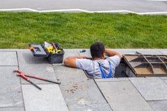 Arbeitskraft, die Reparaturen im Einsteigeloch auf Wasserversorgung durchführt Lizenzfreie Stockbilder