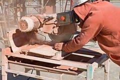 Arbeitskraft, die roten Ziegelstein schneidet Lizenzfreie Stockbilder