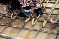 Arbeitskraft, die Stahlwerk für Verstärkung des konkreten Bodens tut Stockfoto