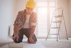 Arbeitskraft, die Tapete befestigt Der Erbauer setzt Kleber auf die Tapete stockfotos