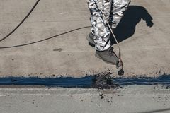 Arbeitskraft, die Teerfolie auf die Dachspitze des Gebäudes installiert Wasserdichtes System durch das Gas- und Feuerin brand set lizenzfreie stockfotografie