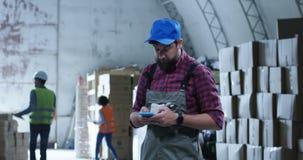 Arbeitskraft, die Telefon in einem Lager verwendet stock video footage