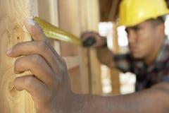 Arbeitskraft, die zwischen Brettern mit Maßband an der Baustelle misst Lizenzfreie Stockfotografie