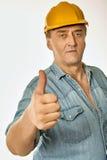 Arbeitskraft in einem gelben Hardhat, der Gestenzustimmung zeigt Stockfotografie