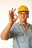 Arbeitskraft in einem gelben Hardhat, der OKAYgeste zeigt Stockfoto