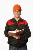Arbeitskraft in einem orange Hardhat schreibt in ein Notizbuch Stockbild