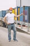 Arbeitskraft in einem Sturzhelm und in einer Schutzmaske steht am Behälter Lizenzfreies Stockfoto