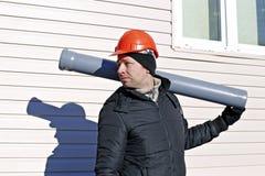 Arbeitskraft an einer Baustelle in einem orange Sturzhelm mit einem Abwasserkanal p Stockbilder