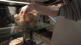 Arbeitskraft in einer Kaffeestube, die Kuchennüsse in ein Paket einsetzt stock video