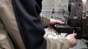 Arbeitskraft entfernt das Teil von der CNC-Drehbankmaschine Drehmaschine für die Bohrung mit dem Bohrgerätwerkzeug und Zentrierbo stock video footage
