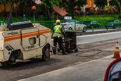 Arbeitskraft füllt einen Handbarrow mit Bitumen und Asphalt Paver Machine Stockfotografie