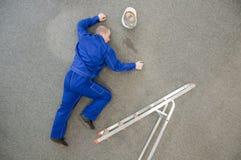 Arbeitskraft fiel von einer Strichleiter stockfotografie