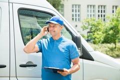 Arbeitskraft in Front Of Truck Writing On-Klemmbrett lizenzfreie stockbilder