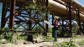 Arbeitskraft im gelben Schutzhelm mit Projektzeichnungen am Kraftwerk stock footage
