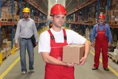 Arbeitskraft im Hardhat mit Paket an der Frontseite des Teams lizenzfreies stockbild