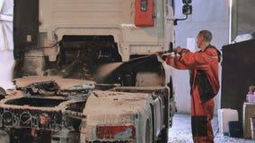 Arbeitskraft im orange Overall pulverisiert Reinigungsmittel auf LKW mit Farbspritzpistole stock footage