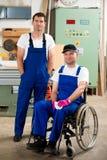 Arbeitskraft im Rollstuhl in der Werkstatt eines Tischlers mit seinem colleagu stockbilder