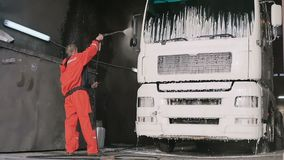 Arbeitskraft im schützenden Overall wäscht LKW mit Wasser in slowmotion stock footage