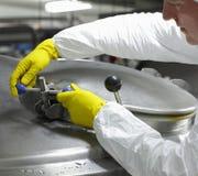 Arbeitskraft im schließend Behälter des industriellen Prozesses der gelben Handschuhe Stockfotos
