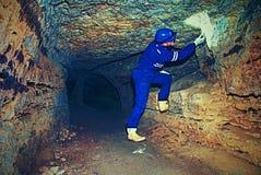 Arbeitskraft im Tunnel Personal in einer Schutzanzugkontrolle sedimentiert in der felsigen Wand Stockbild