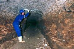 Arbeitskraft im Tunnel Personal in einer Schutzanzugkontrolle sedimentiert in der felsigen Wand Lizenzfreie Stockbilder