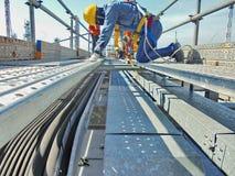 Arbeitskraft installieren Kabelbehälter stockbild