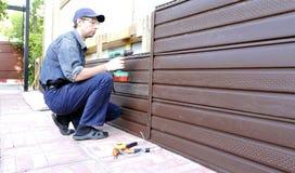 Arbeitskraft installiert Plastikabstellgleis auf die Fassade Stockfotografie