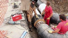 Arbeitskraft ist justieren das Werkzeug, das auf Rohr für das Schweißen von zwei Rohren gesetzt wird stock video footage