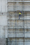 Arbeitskraft klettert am Bau in der Baustelle Lizenzfreie Stockbilder