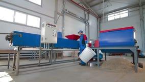 Arbeitskraft lädt geschnittenen Plastik in automatisierter Plastikwiederverwertungsmaschine stock video