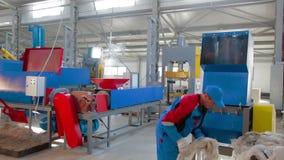 Arbeitskraft lädt sortierten Plastik in automatisierter Plastikwiederverwertungsmaschine stock video