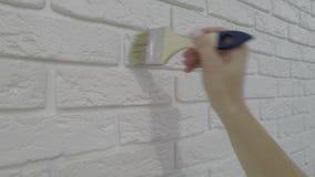 Arbeitskraft lackiert manuell dekorativen Ziegelstein auf der Wand stock video footage