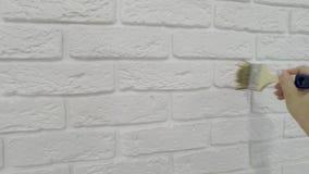 Arbeitskraft lackiert manuell dekorativen Ziegelstein auf der Wand stock video