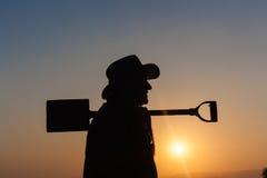 Arbeitskraft-Mann-Sonnenuntergang-Schattenbild Lizenzfreies Stockfoto