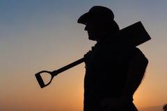 Arbeitskraft-Mann-Sonnenuntergang-Schattenbild Stockfotografie