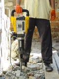 Arbeitskraft mit dem Demolierungshammer, der Innenwand bricht stockbild
