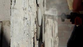 Arbeitskraft mit dem Demolierungshammer, der Innenwand bricht stock footage