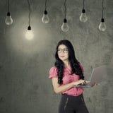 Arbeitskraft mit dem Laptop, der Glühlampe betrachtet Stockbild