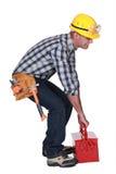 Arbeitskraft mit einem schweren Werkzeugkasten Stockbild