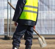 Arbeitskraft mit einer Schaufel an der Baustelle lizenzfreie stockbilder