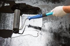 Arbeitskraft mit Farbenrolle tun bedeckte Böden Stockfotografie