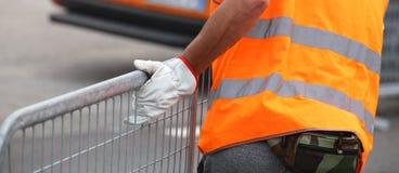 Arbeitskraft mit hoher Sichtsicherheitsweste und -handschuhen Stockfotos