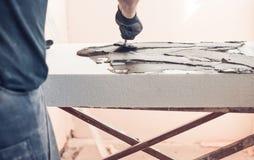 Arbeitskraft mit Kellebedeckungsschaumstoff Stockbilder