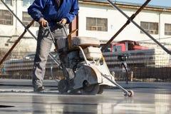 Arbeitskraft mit konkreter Schneidemaschine in der Bewegung Stockbilder