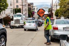 Arbeitskraft mit LANGSAMEM Zeichen auf der Straße Lizenzfreie Stockfotografie