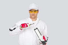 Arbeitskraft mit Messer löschen Schnittschutzkappen-Dichtungsmittelsilikon Stockfoto