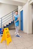 Arbeitskraft mit Reinigungs-Ausrüstungen und nassem Boden-Zeichen Stockfoto
