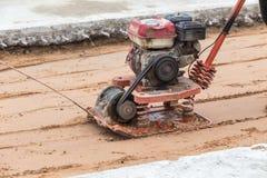 Arbeitskraft mit roten Bodenverdichtern in der Baustelle lizenzfreie stockfotos