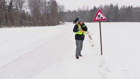 Arbeitskraft mit Schneeschaufel nahe Verkehrsschild stock video footage